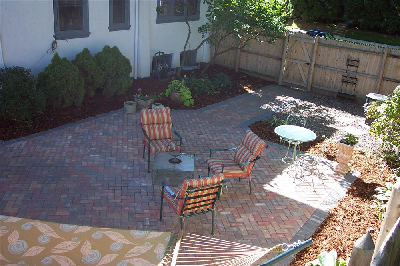outdoor living space in small Milwaukee backyard featuring a paver patio and landscaping