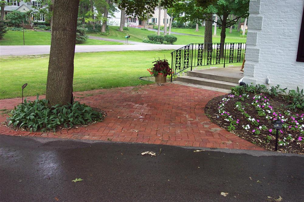 Elm Grove outdoor hardscaping designs include red brick additions, entrance pathways, and patio areas