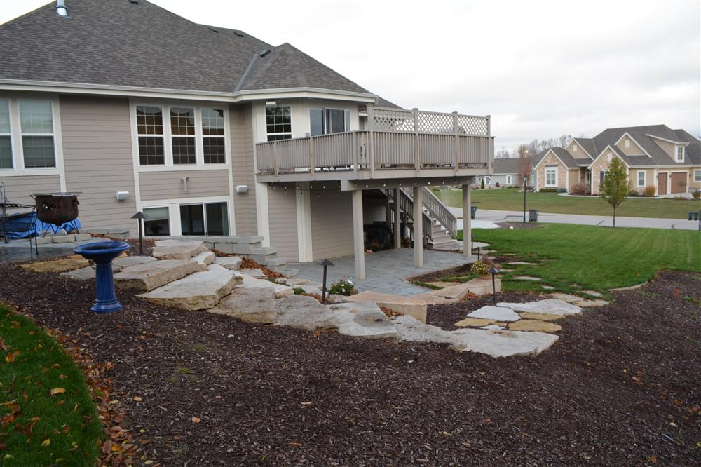 Stone patio and rock retaining wall with stairs in Pewaukee from Loomis Landscaping